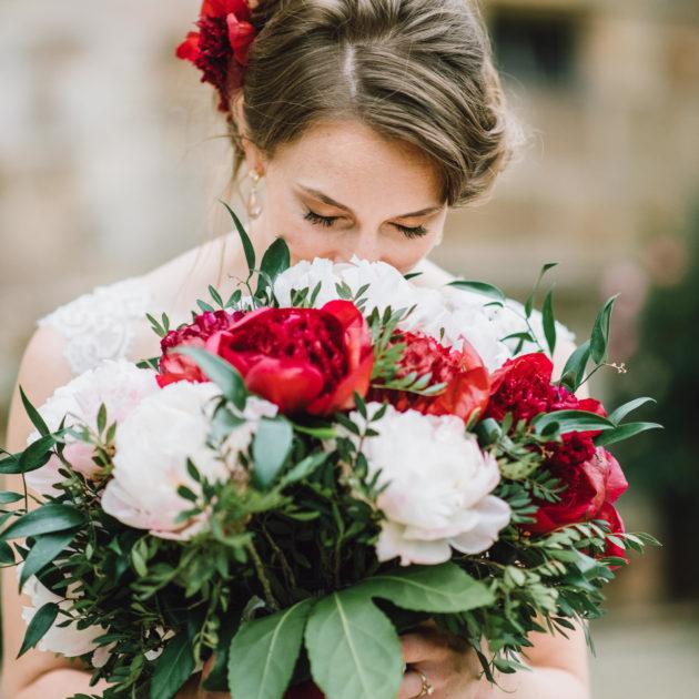 Braut schnuppert an riesigem Brautstrauß mit Pfingstrosen