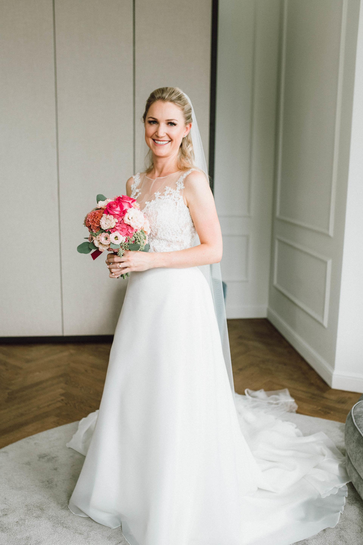 Strahlende Braut mit pinkem Brautstrauß