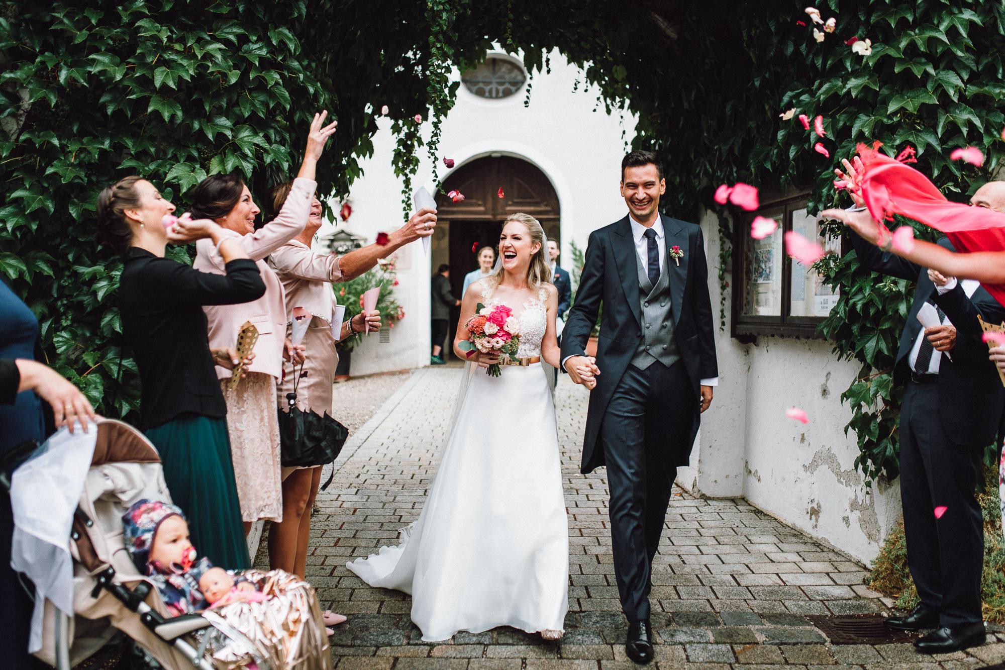 Strahlendes Brautpaar im Blütenregen