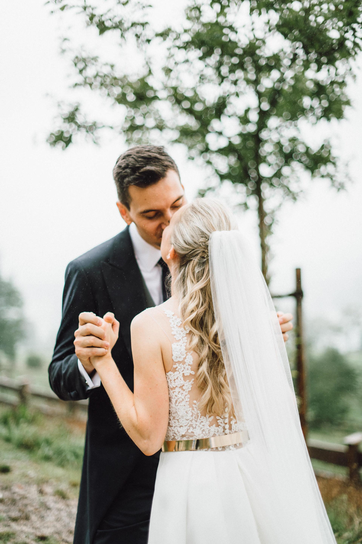 Kuss zwischen dem Brautpaar im Regen